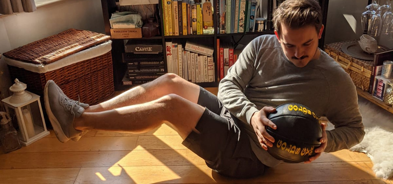 A man doing Russian twists with a medicine ball in his living room