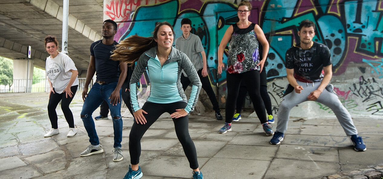 A groups of people doing exercise outside, in front of a graffiti mural
