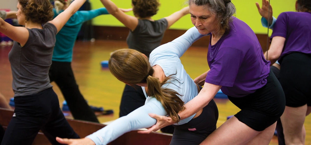 A woman helps another with a pose in a yoga class