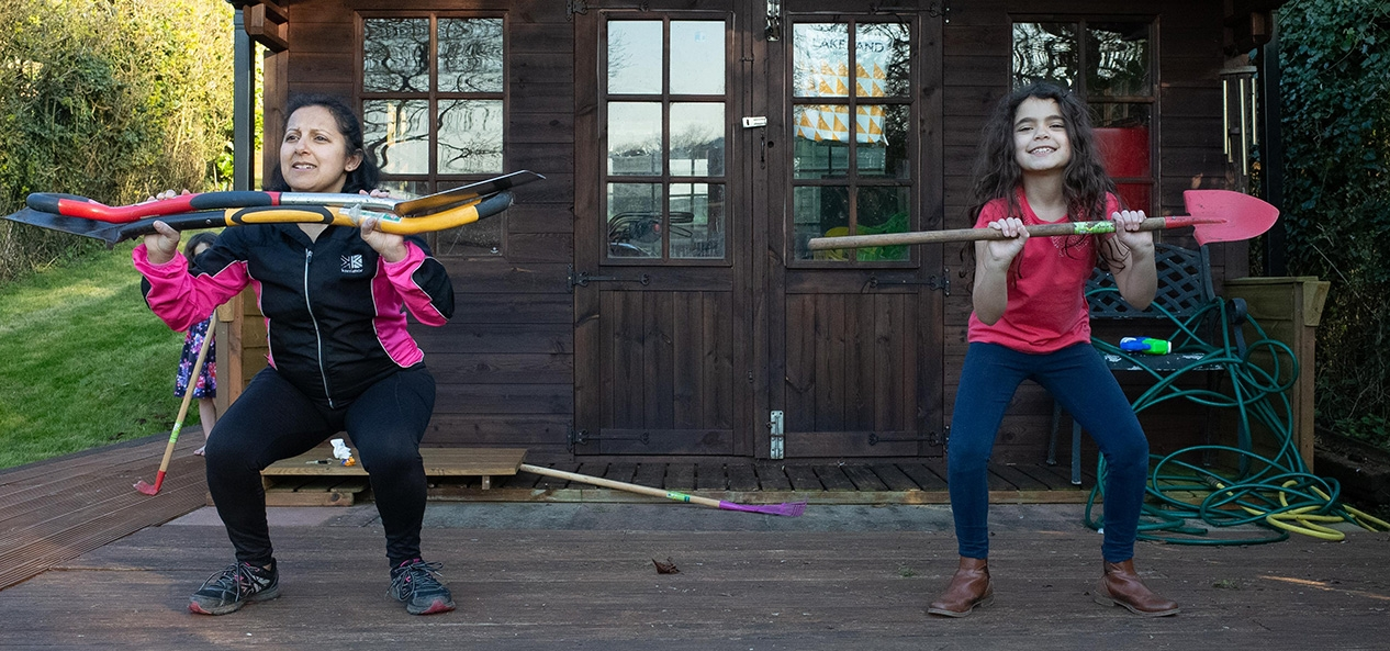 A mother and daughter exercise in their garden, using garden tools as weights