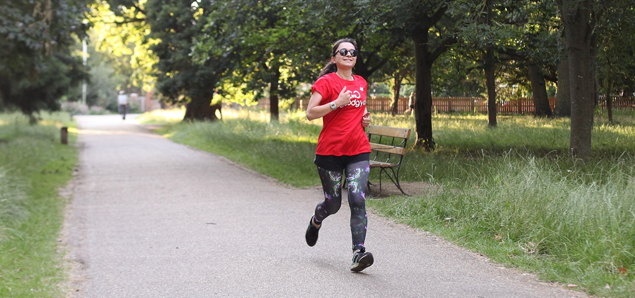 A woman runs alone in a park, wearing a Good Gym t-shirt