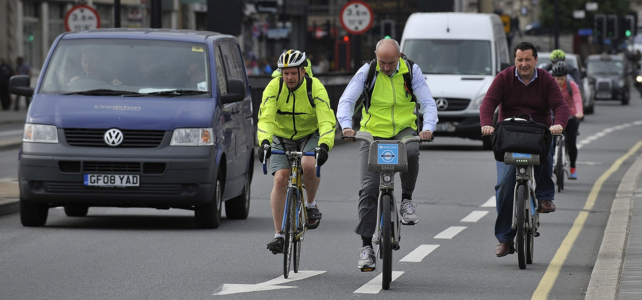 Cyclists, some on public hire bikes, share the road with cars in a city centre