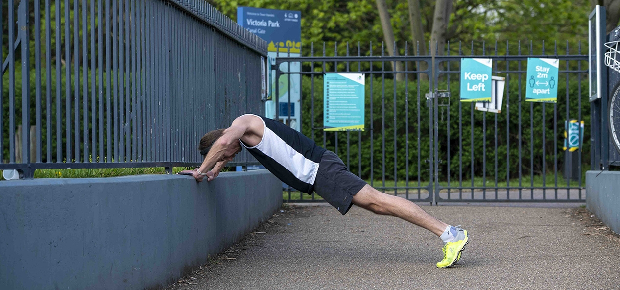 A man leans on a wall outside a park to stretch