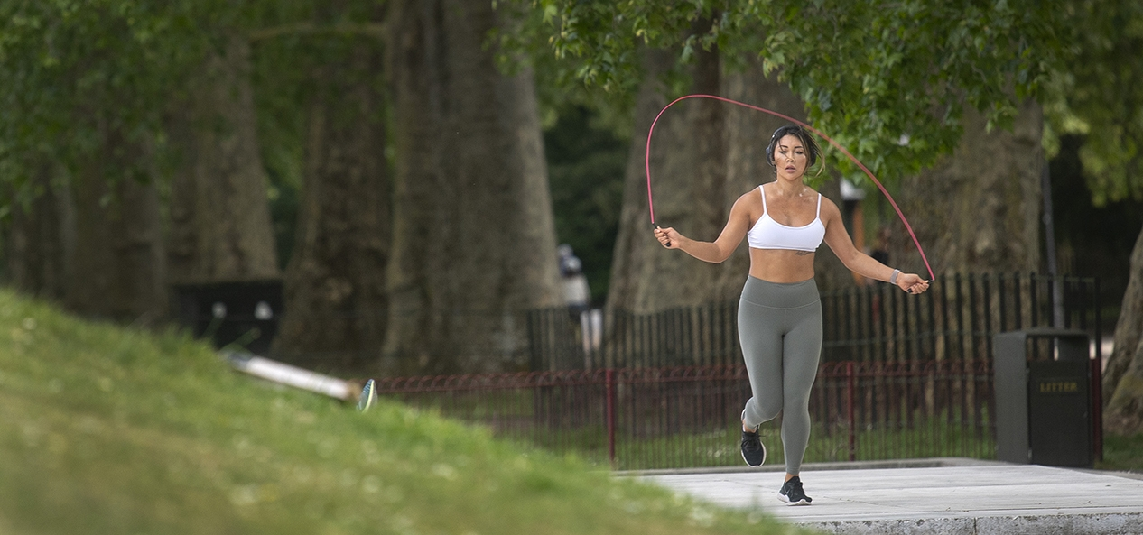 A women skips in the park