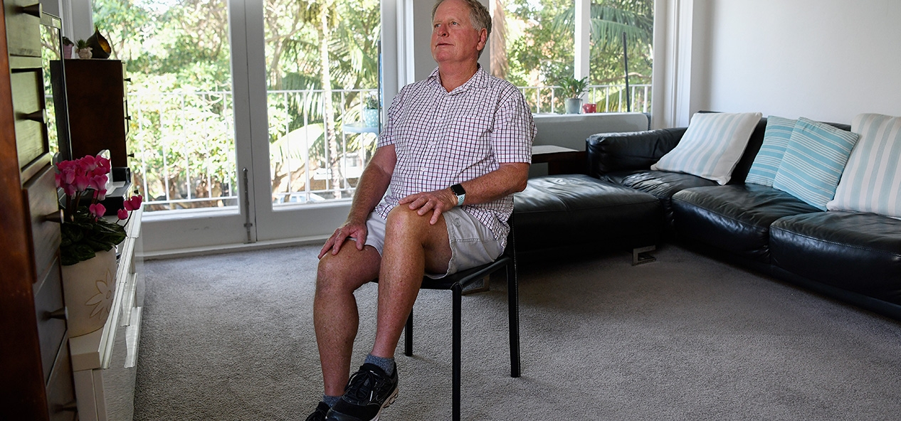 An older man performs seated exercises in his home.