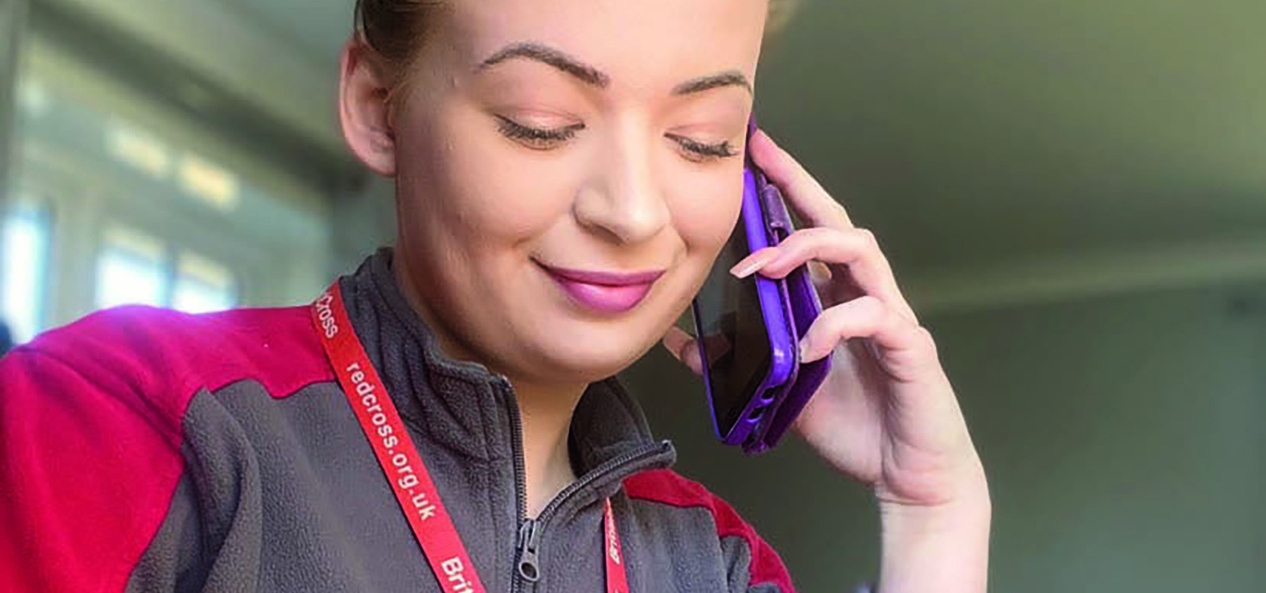 A British Red Cross volunteer on the phone.