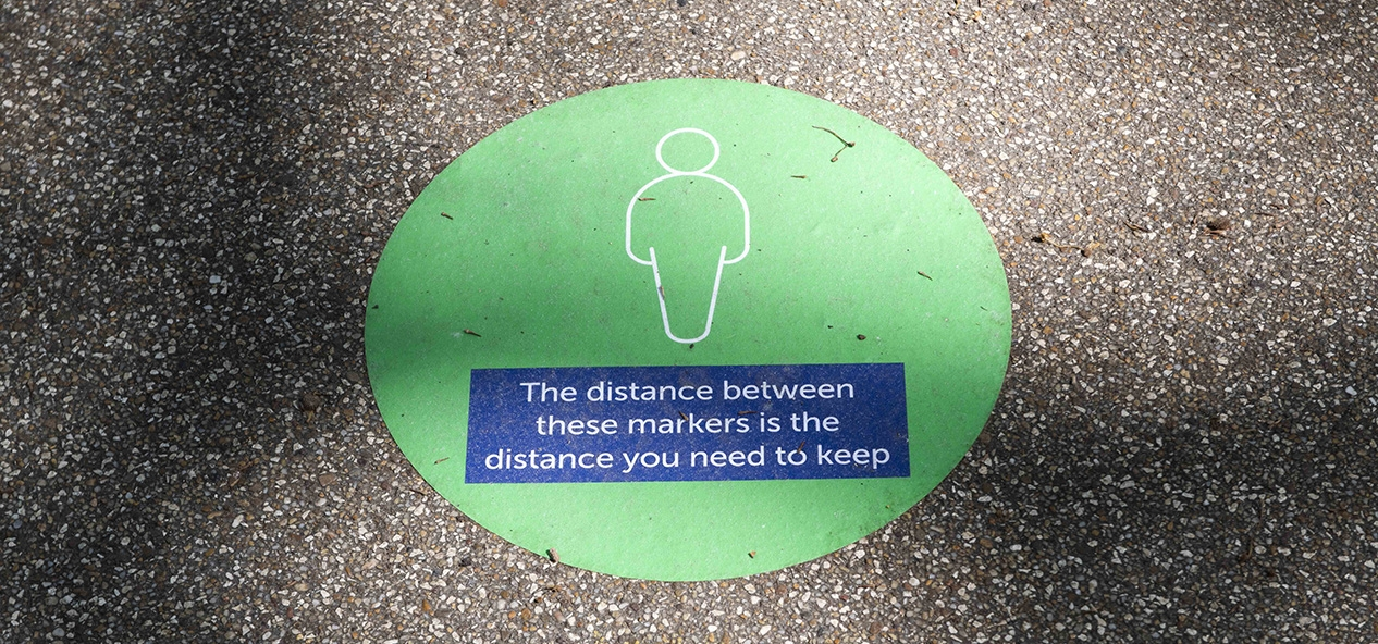 A painted sign on the ground instructing people to keep two metres apart.