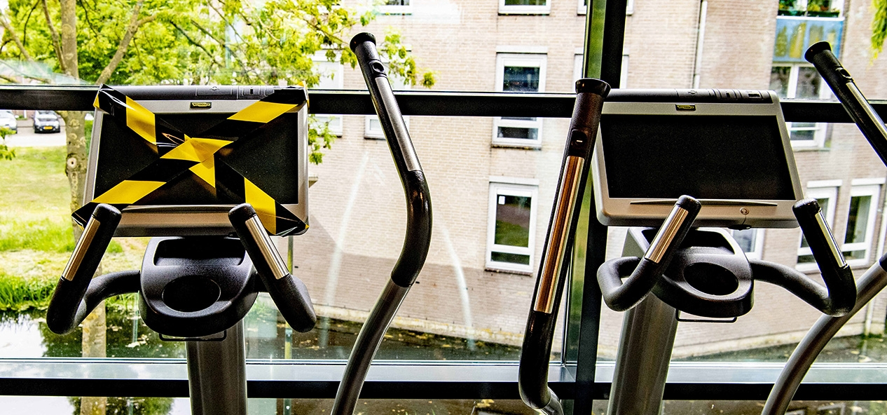 An indoor gym with tape over some machines to enable social distancing