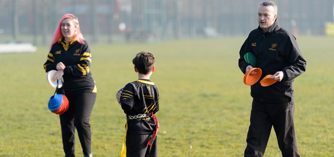 Two volunteers talking to a child on a playing field.