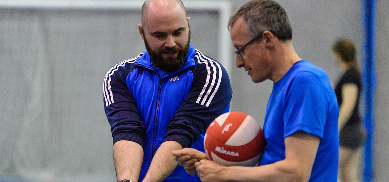 A volleyball coach demonstrates the technique for a dig shot.