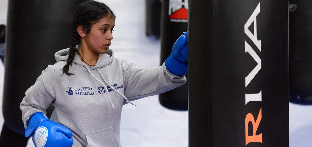 A woman hitting a punching bag.