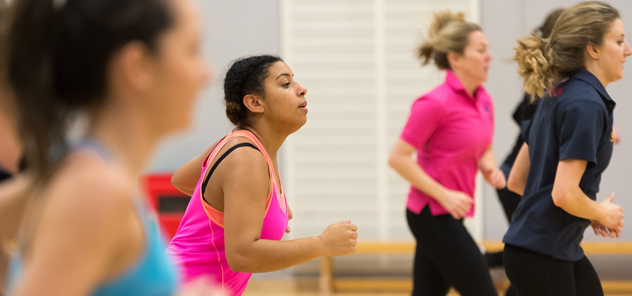 A group of women train for netball in an indoor hall.