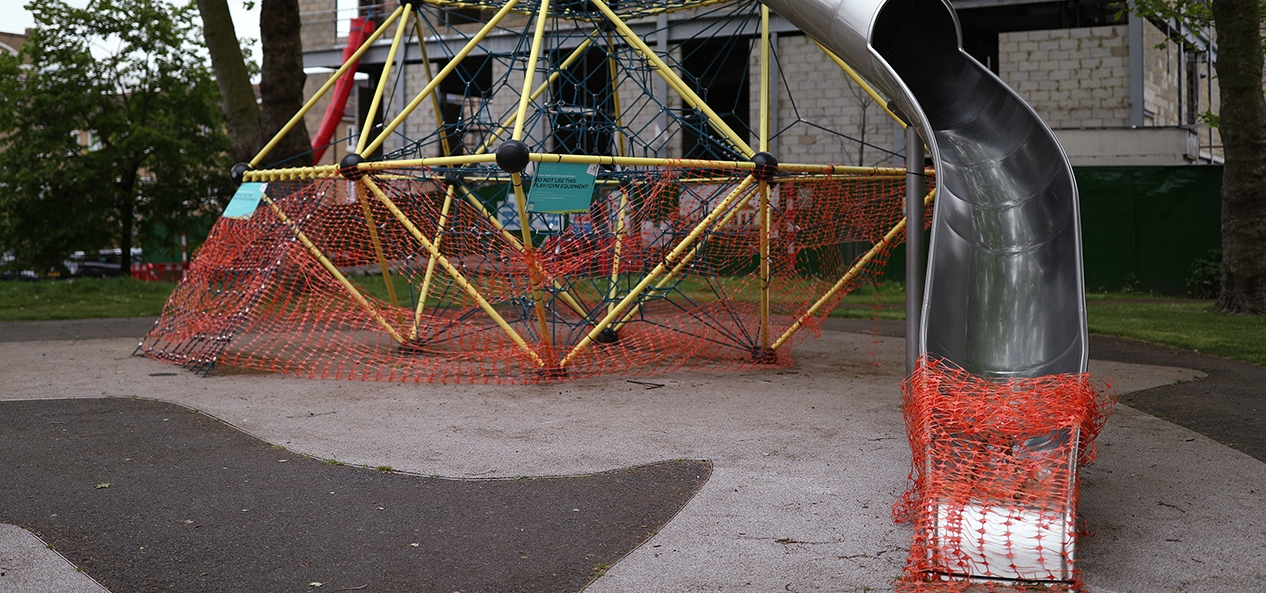 A closed playground with netting over the bottom of a slide