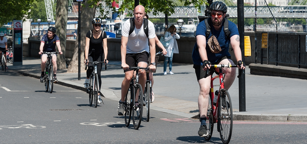 Cyclists ride in a line through a city.