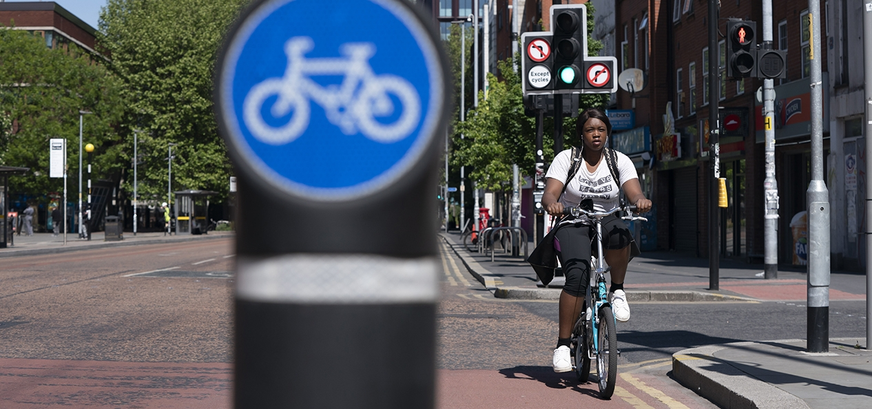 A woman cycles in a cycle lane in Manchester.