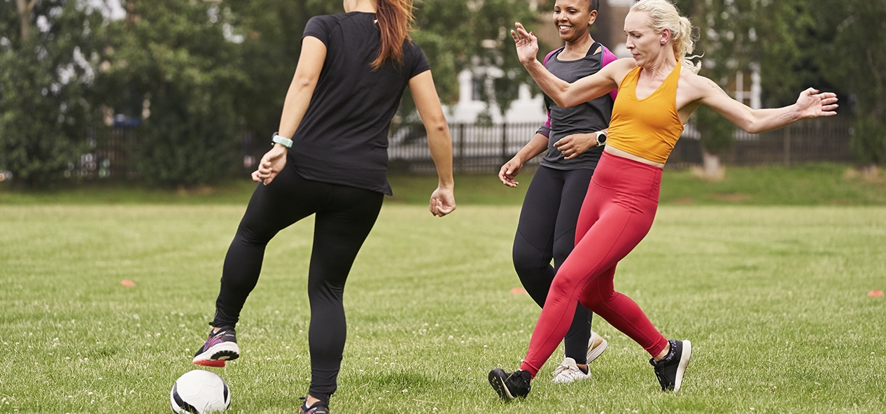 A group of women playing football in a park.