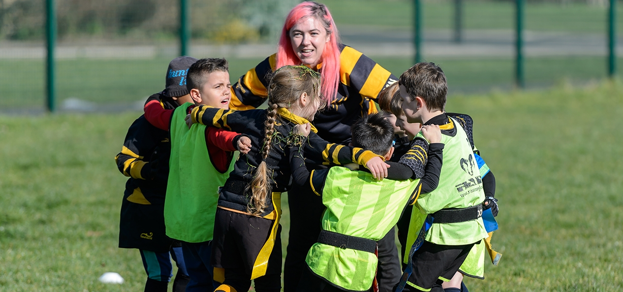 A rugby coach speak to a group of children who have formed a huddle around her.