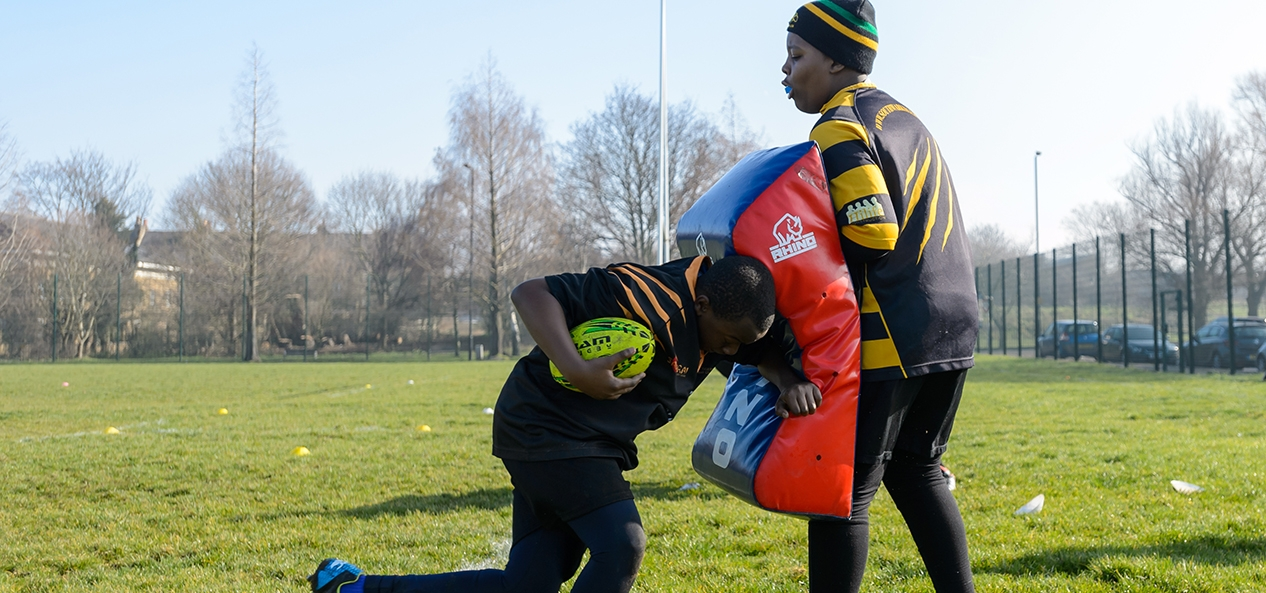 Two rugby players perform a tackling drill with one holding a tackling pad