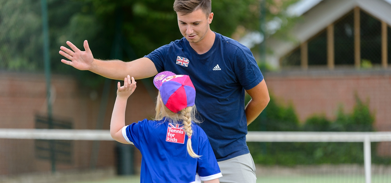 A tennis coach high fives a girl during a training session
