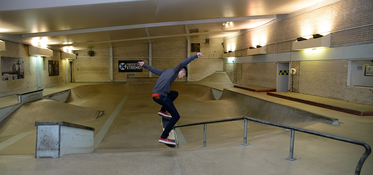 A boy skates in in a swimming pool that's been converted into a skate park