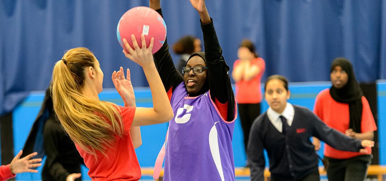 A group of schoolchildren playing netball inside a sports hall.