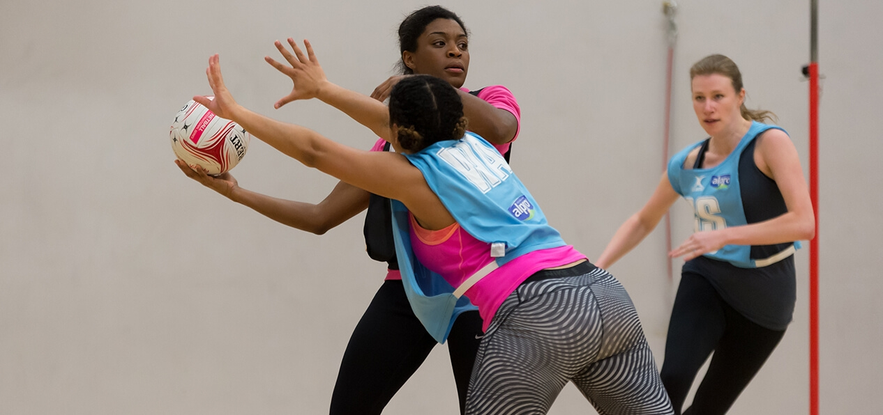 Three women playing netball in an indoor sports hall.