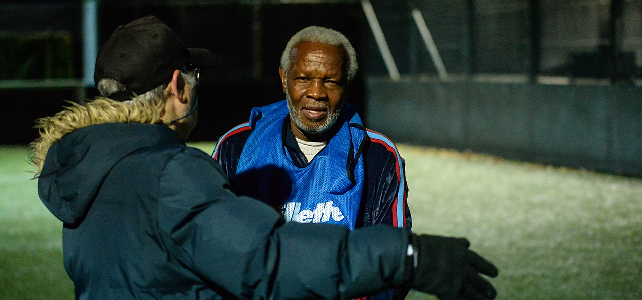 A coach gives instructions at a walking football session.