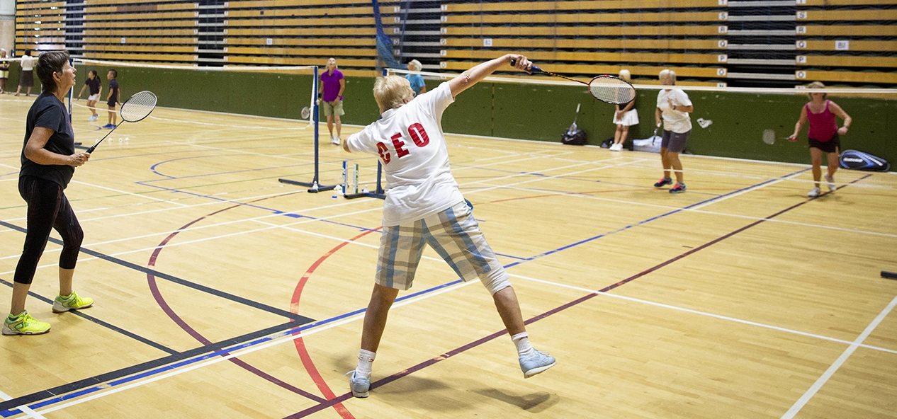 People play badminton in a sports hall