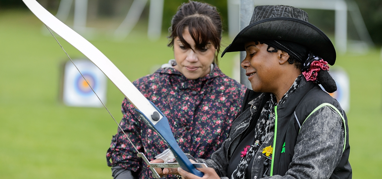 A female archery coach instructs another woman at an archery lesson outdoors.