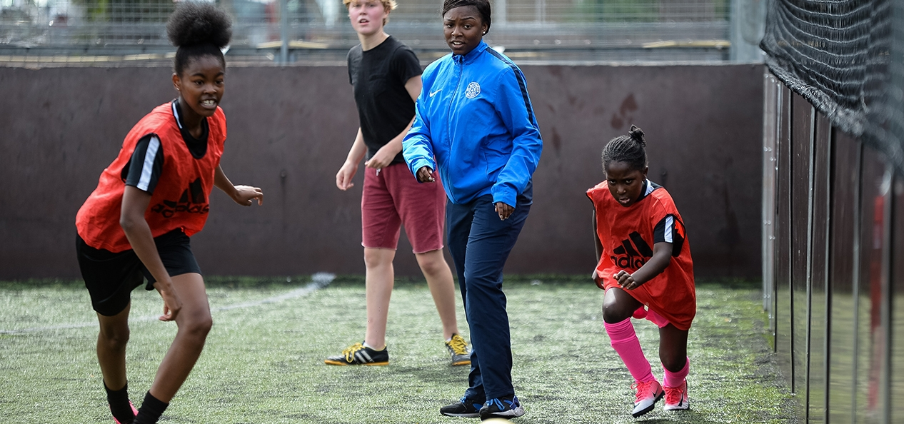 A coach watches on during a football session on a five-a-side pitch