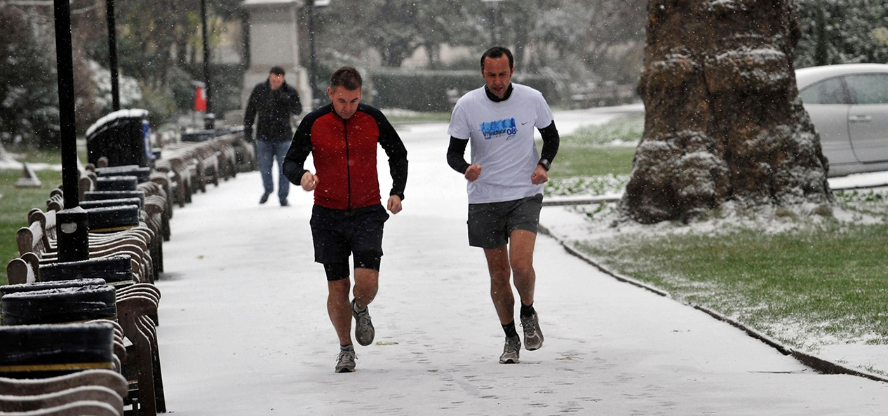 Two joggers exercise in the snow