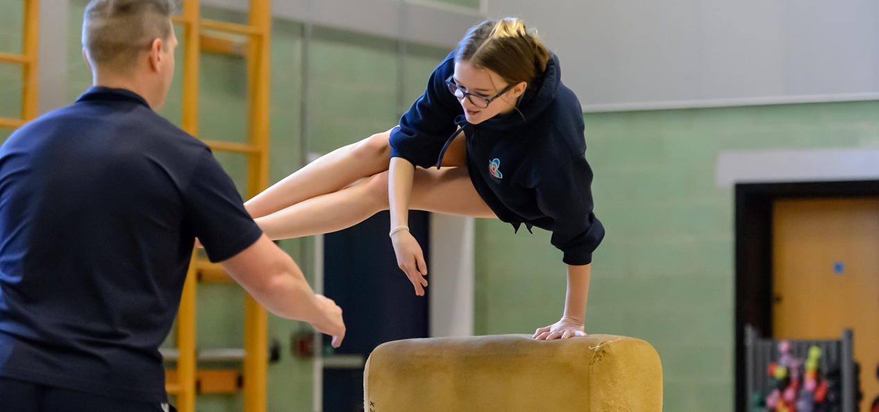 A school girl vaults over a horse in a school PE class, while her teacher waits to catch her if she falls.
