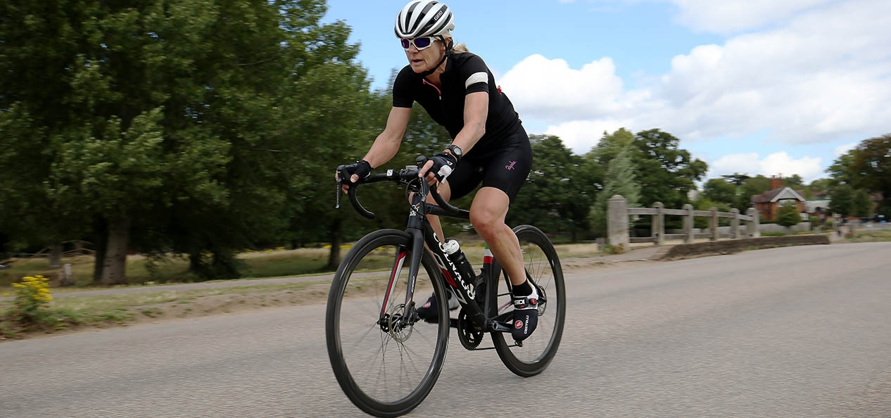 A woman rides a racing bike through Richmond Park, London.