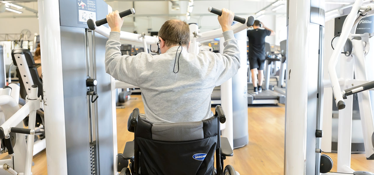 A man in a wheelchair uses a lat pull down machine in a gym.