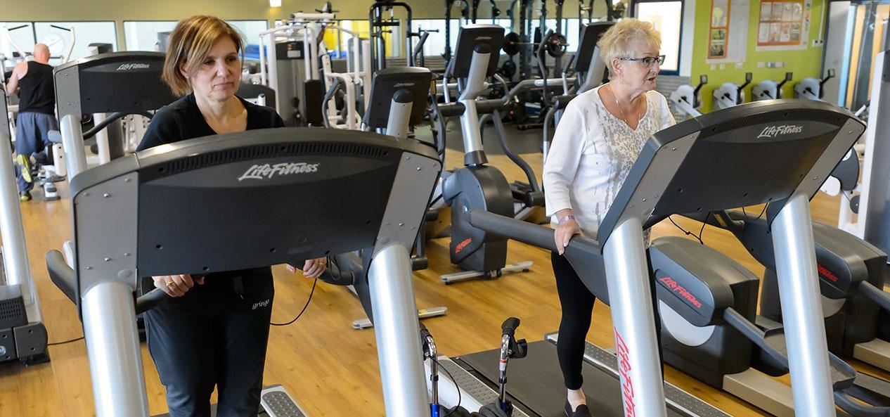 Two women walk on treadmills in a gym