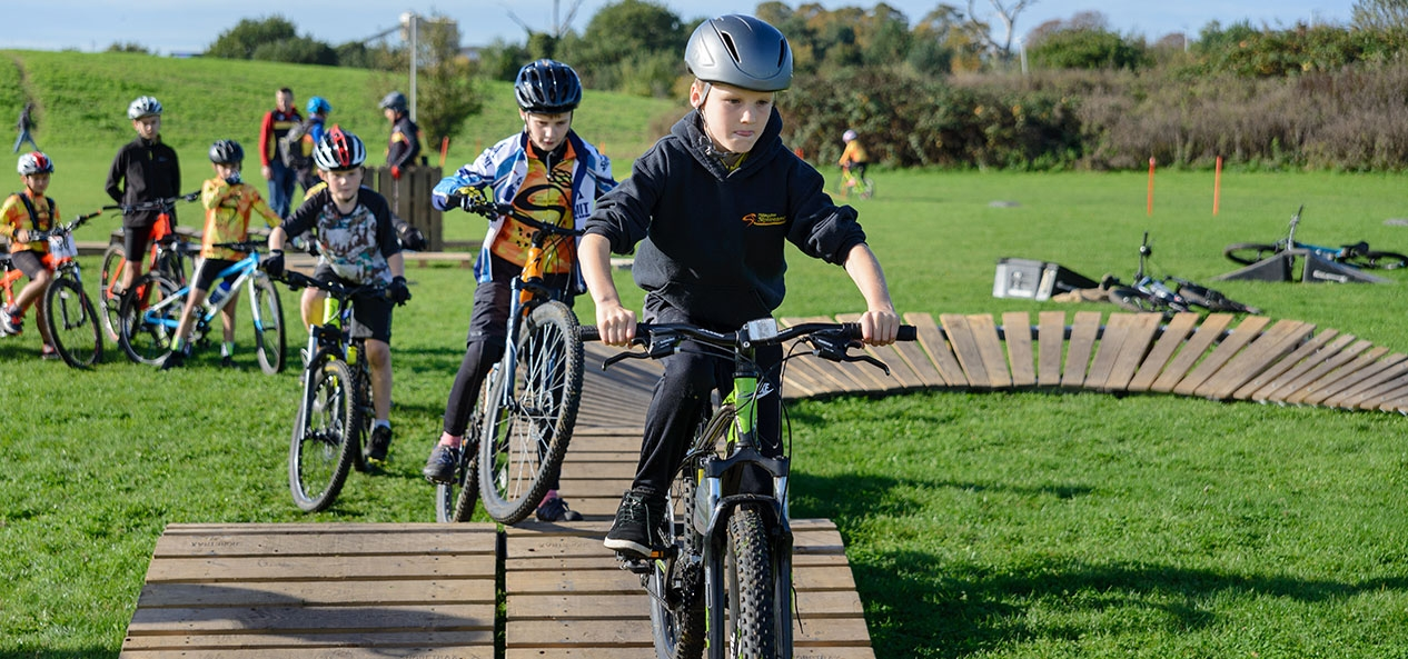 A junior cycling coaching session with mountain bikers learning to ride a wooden pump track