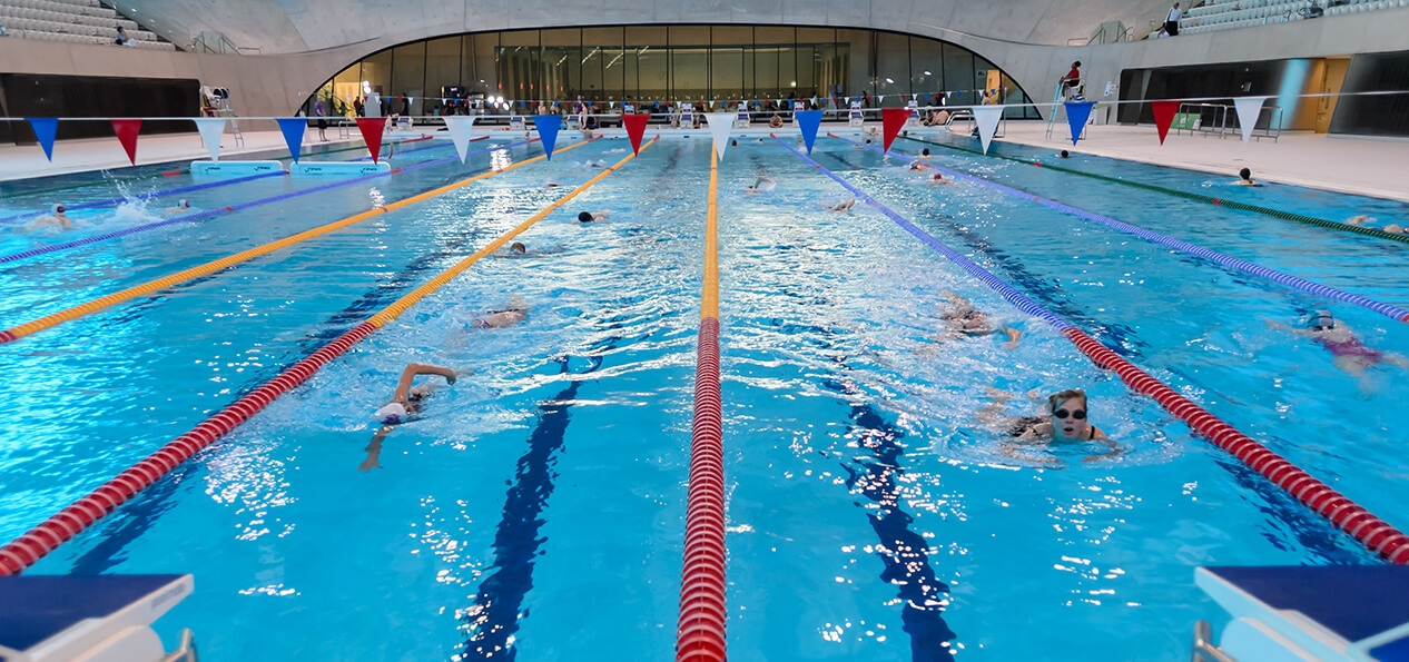 People swimming in the London Aquatics Centre pool