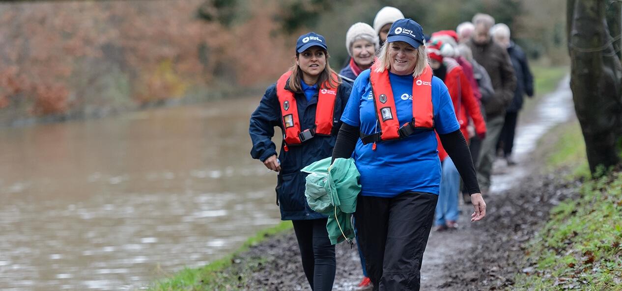 A group of people walking alongside a canal.