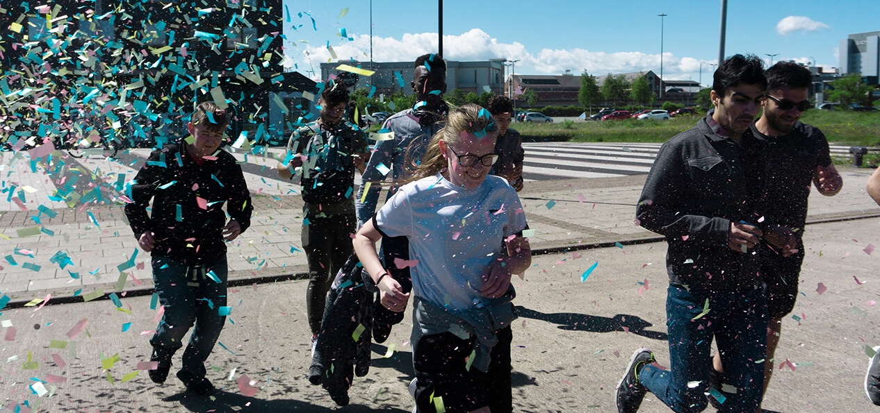 A group of schoolchildren smiling as they run through falling confetti.