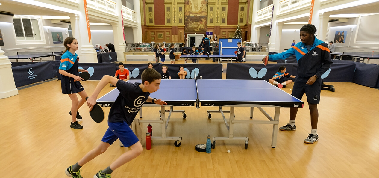 A boy runs around a table tennis table during a game.