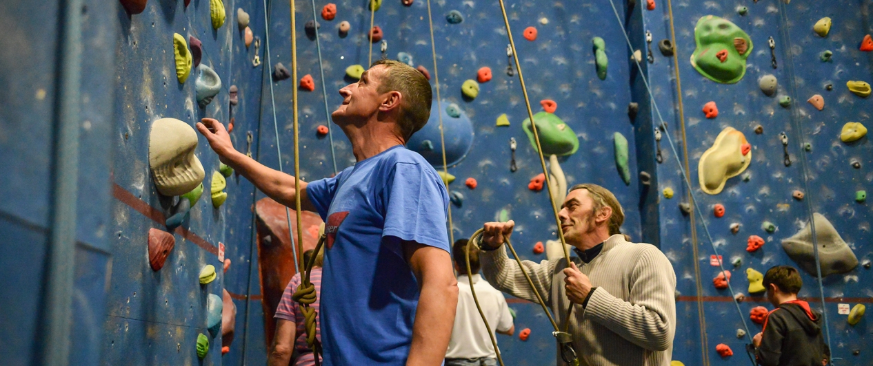 A man looks up a climbing wall as he and others prepare to climb it.