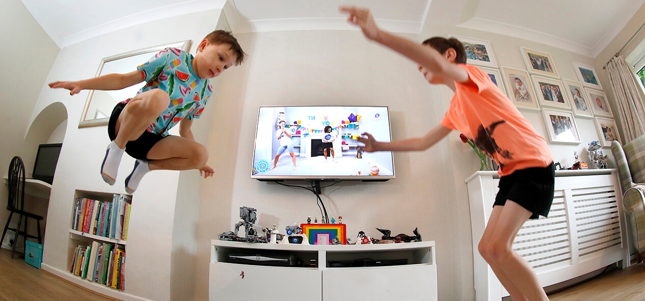 Two boys jumping as they follow along with a Joe Wicks workout playing on the TV behind them.