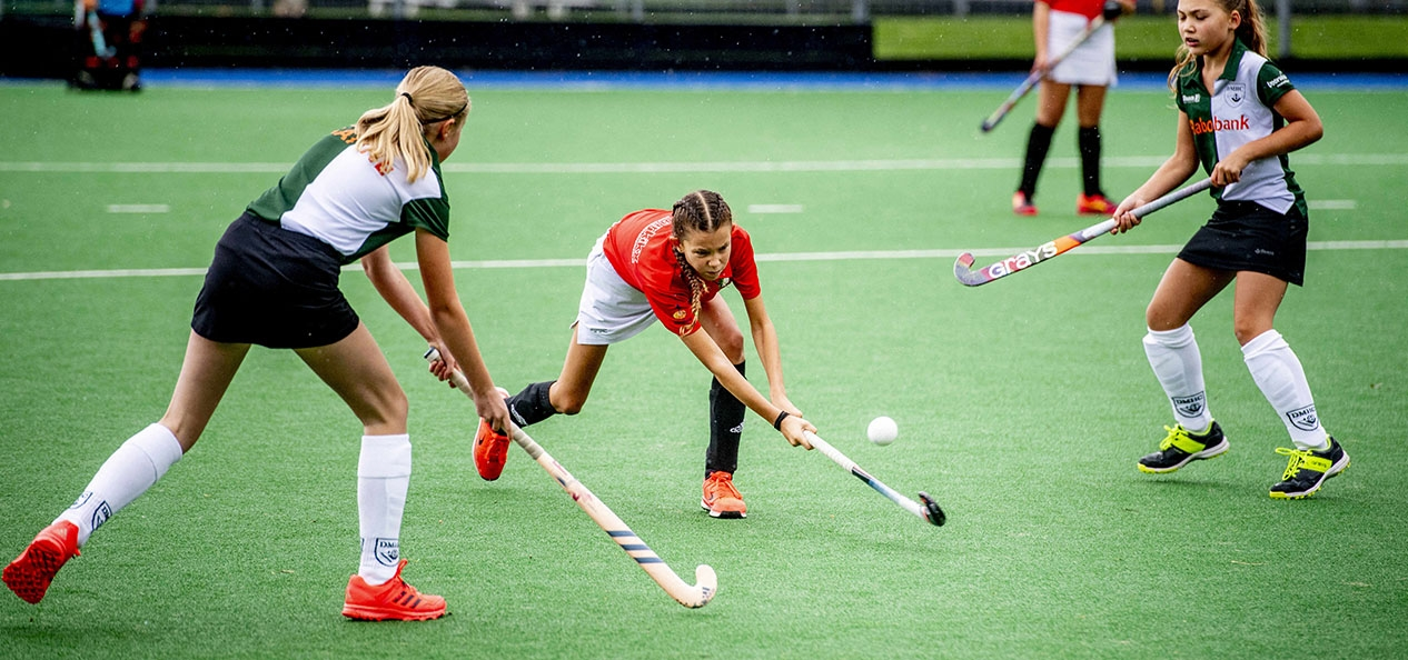 A girls' hockey match with one girl hitting the ball as opposition players close her down.