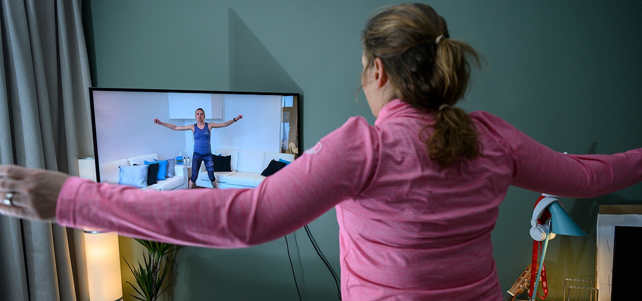 A woman following a home workout she's watching on her TV.
