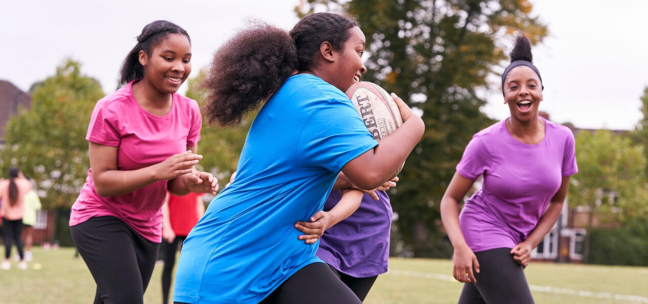 A girl runs with a rugby ball as three other players follow her.