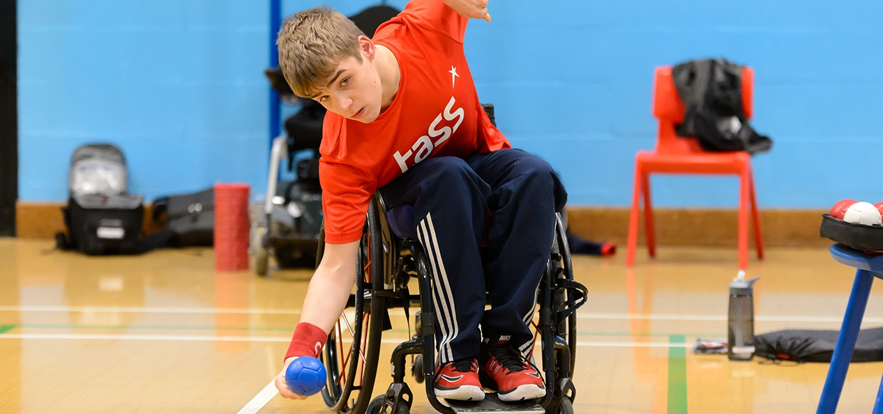 A young man in a wheelchair playing boccia in a sports hall.