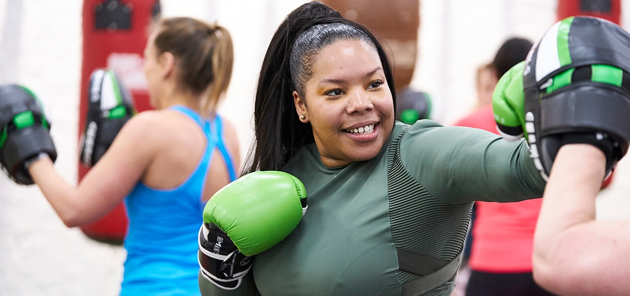 A woman practicing some boxing shots at an indoor session.
