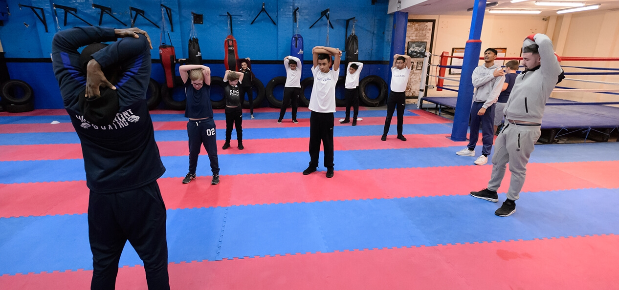 A group of people stretching as part of a warm up in a boxing hall.