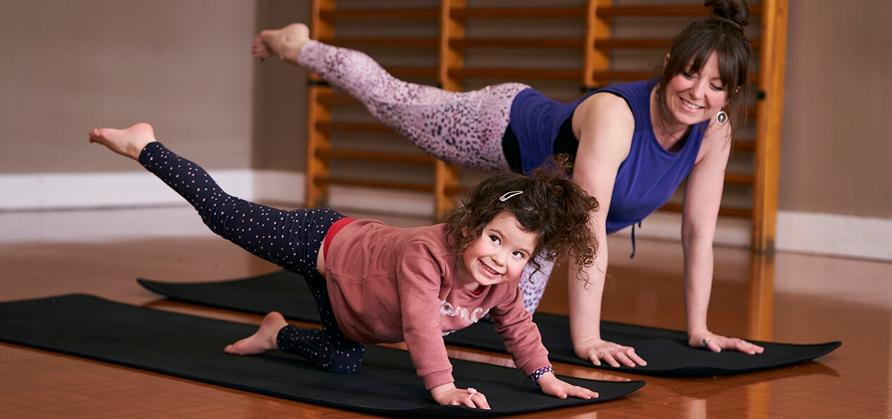 A mother and her daughter smile as they do yoga in an indoor hall.