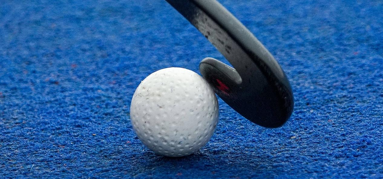 A close up of the head of a hockey stick on a hockey ball - on a blue hockey pitch